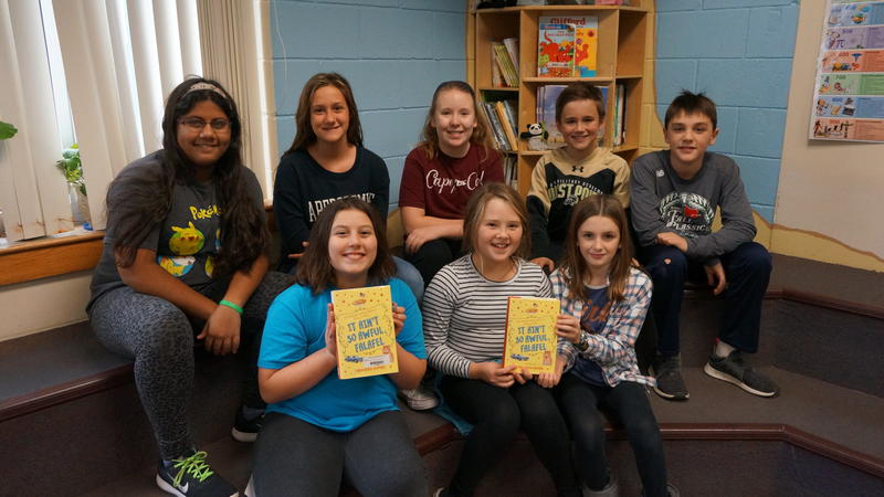 Eight students sit in a library holding up copies of Firoozeh's Dumas' novel