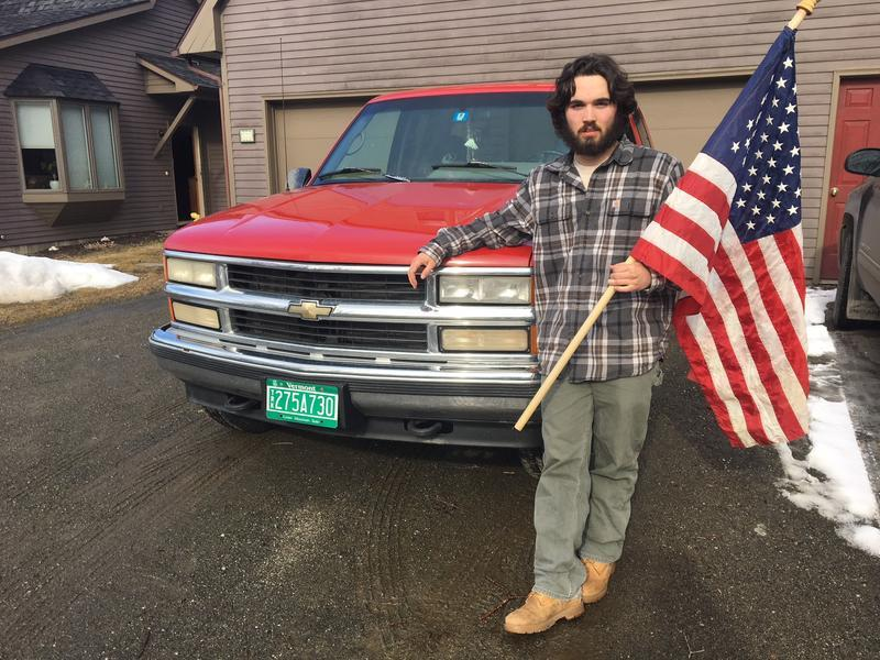 Stowe High School student Sam Robertson holds an American flag and stands in front of a truck.