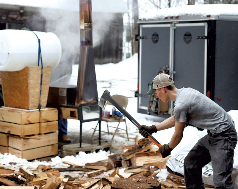 A student at the Thetford Outdoor Program chops wood to fuel an evaporator for maple sugaring.