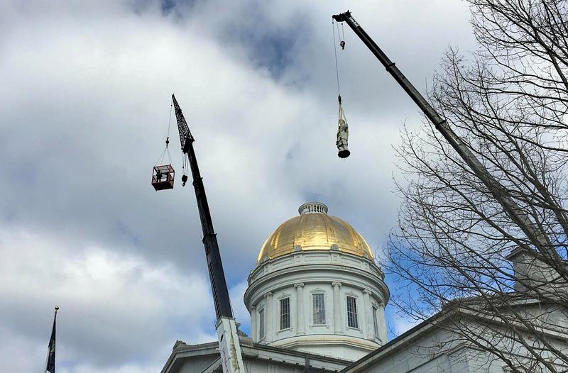 Two cranes lift the 14-foot statue of Ceres, the Roman goddess of agriculture, from the capitol dome as part of $2 million rennovation project.
