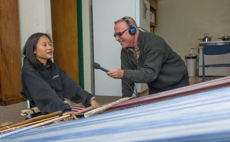 Greg Sharrow, right, interviews Burmese weaving instructor True Tender Htun as she demonstrators the use of homemade looms she used in Burma and now in Vermont.
