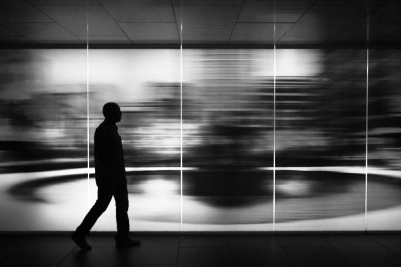 A silhouette of John Nyembo walks against a blurry background in a black-and-white photograph