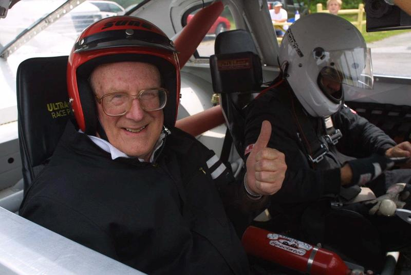 Then-Sen. Phil Scott, right, takes then-Sen. Bill Doyle for a racecar drive back in June 2001. Both have helmets on, Doyle is smiling and giving a thumbs up.