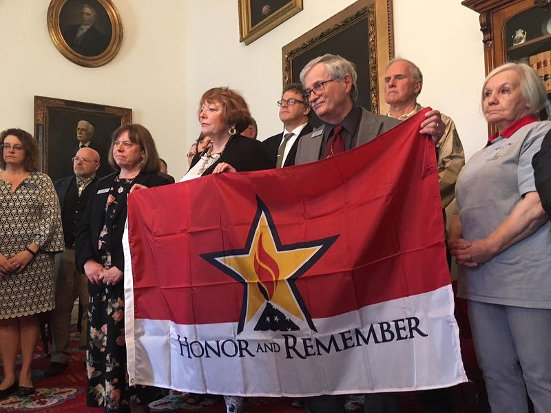 "Lawmakers hold up the ""Honor and Remember"" flag during a bill signing ceremony Thursday. The flag will honor Vermonters who died as a result of their military service."