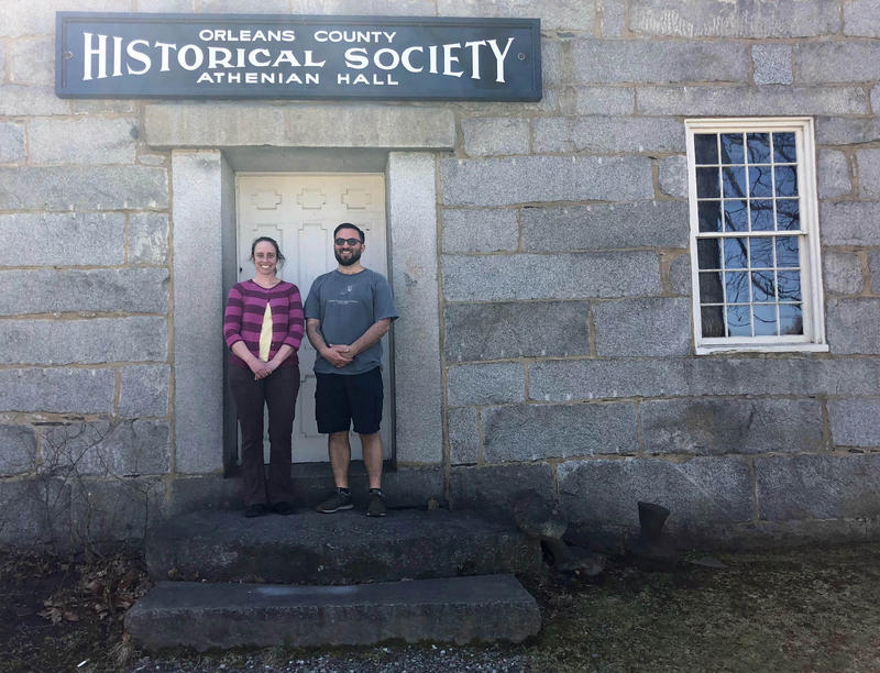 Old Stone House Museum Director Molly Veysey and Deputy Director Walter Parenteau stand in front of the Orleans County Historical Society building and under the sign.