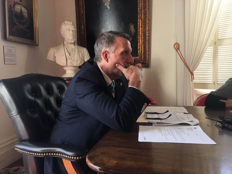 Gov. Phil Scott listens Monday as economists deliver the latest revenue forecast. Scott wants to use this year's budget surplus to buy down property tax rates next year. Democratic lawmakers say the money can be put to better uses.