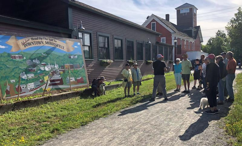 A crowd gathers behind the old Morrisville Depot, where the Lamoille Valley Rail Trail now passes through downtown Morrisville. They're there for an informal tour of the village's new History & Art Walk.