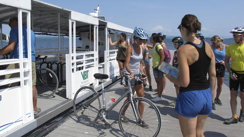 Cyclists disembark from a bike ferry in South Hero, Vermont on a blue-sky day.