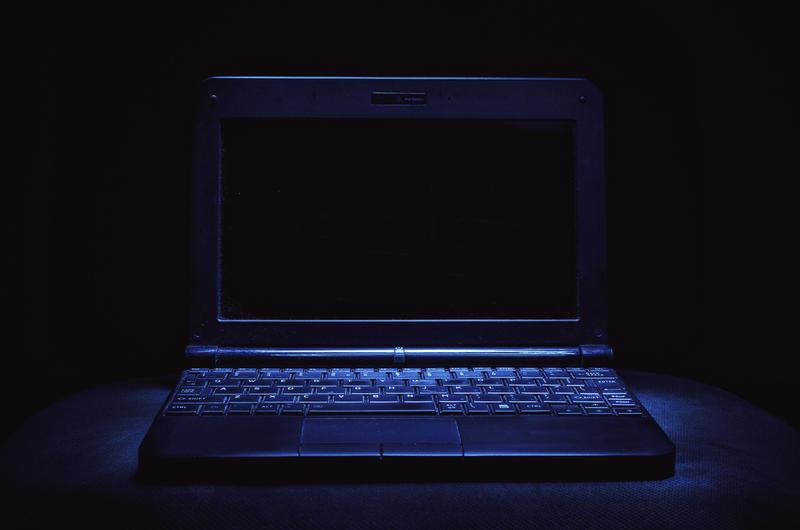 An open laptop on a surface in a dark room.