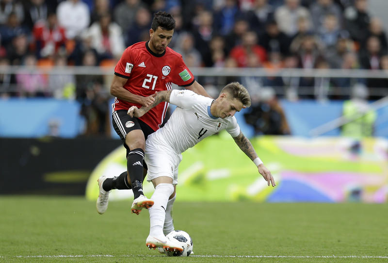Two soccer players fight for control of the ball.