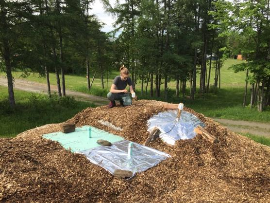 Hannah Weiss installing automated temperature sensors on a snow pile at Craftsbury Outdoor Center.