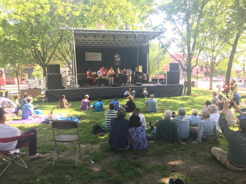 The Makanda Project plays at City Hall Park in Burlington on a stage while people sit on the lawn and watch.