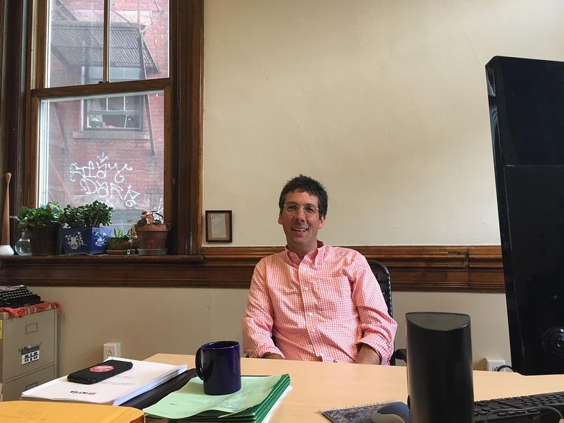 James Lyall, executive director of the ACLU of Vermont, seated as a desk