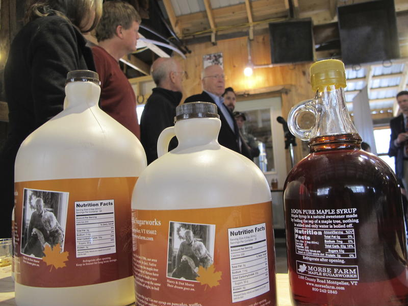 Bottles of maple syrup are lined up on a table, their nutrion facts visible, while Rep. Peter Welch and Sen. Patrick Leahy stand in the background.