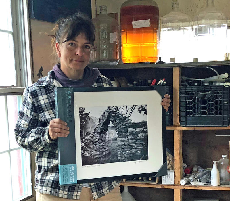 Thea Alvin holds a photo of her old barn, framed behind a gothic arch she built. The barn burned down in December, but the arch still stands. A community member stopped by and gave her the photo last week.