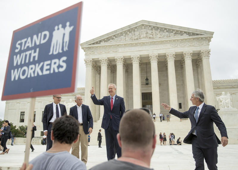 Illinois Gov. Bruce Rauner gives a thumbs up outside the Supreme Court, Wednesday, in Washington. The Supreme Court ruled Wednesday that government workers can't be forced to contribute to labor unions that represent them in collective bargaining.