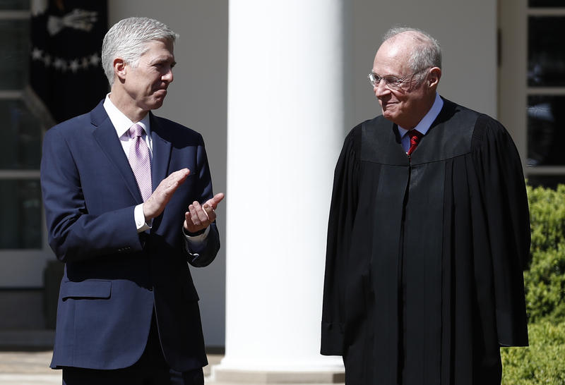 Supreme Court Justice Neil Gorsuch stands looking at Justice Anthony Kennedy in April 2017.
