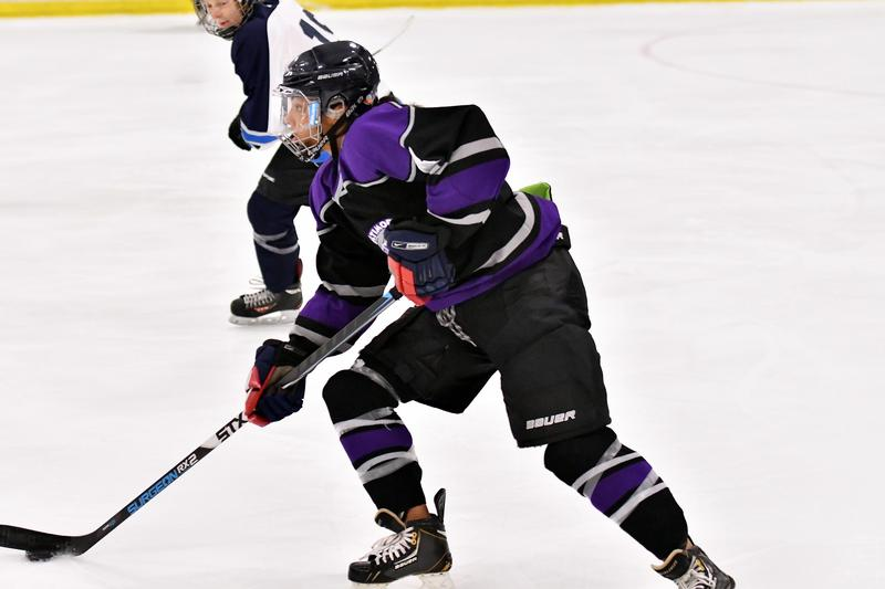 Jasmine Bazinet-Phillips stickhandles in hockey gear on a rink surface while another player watches