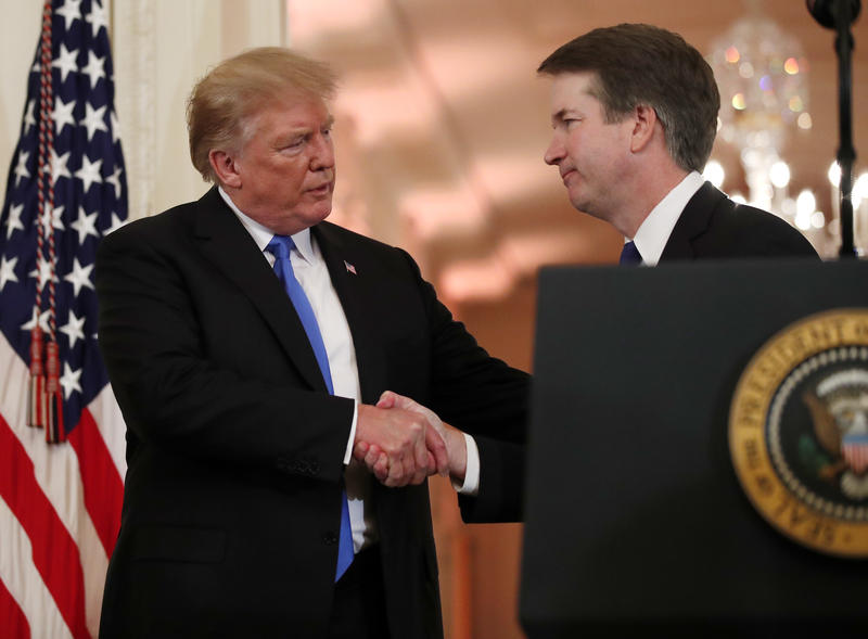 President Donald Trump shakes hands with Brett Kavanaugh.