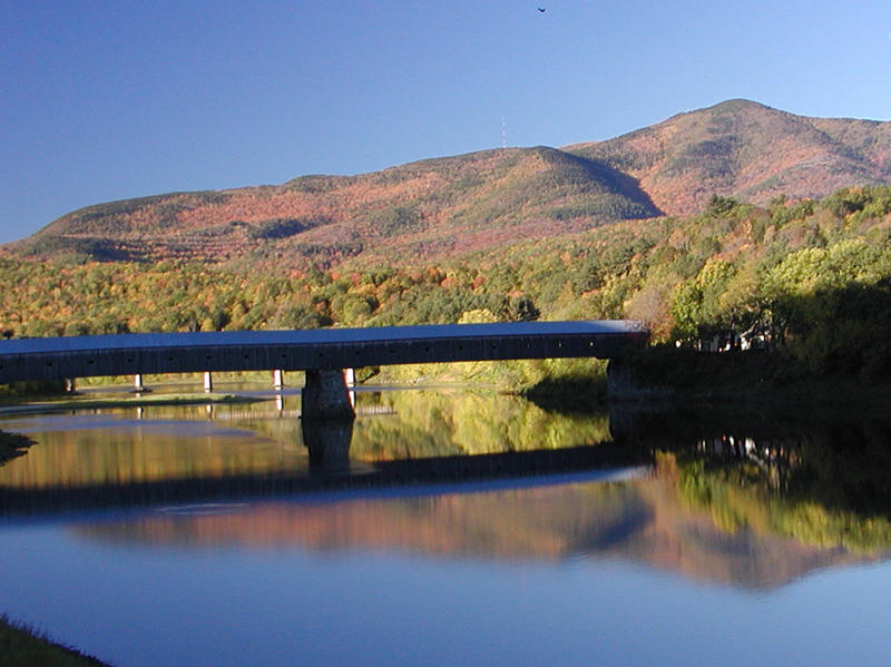 Mount Ascutney in the fall with a covered bridge crossing a body of water.