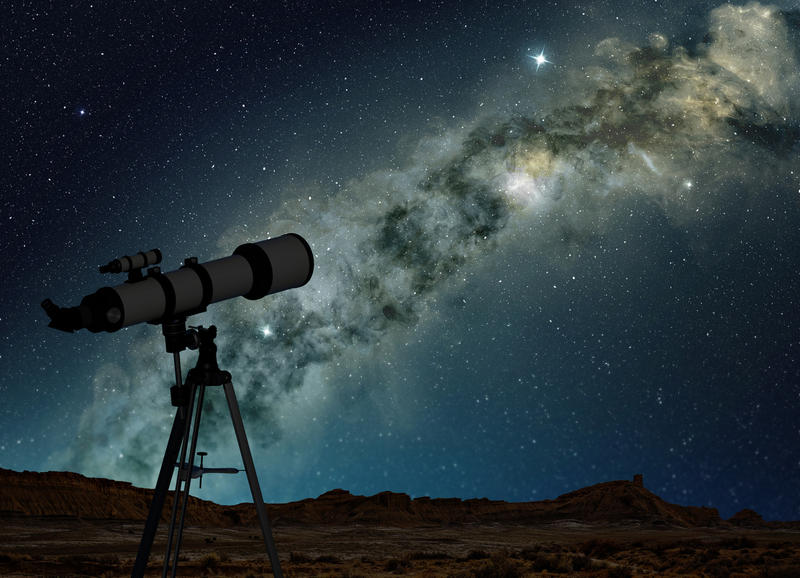 A telescope on a tripod pointed up toward a night sky.