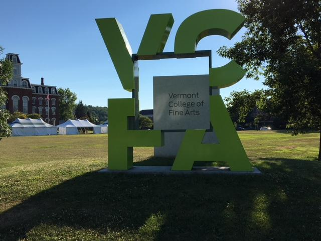 VCFA sign in Montpelier, the letters surrounding the name Vermont College of Fine Arts with a building in the background.