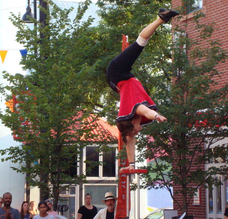 Catherine Flaherty does a one-handed handstand on top of pedastal on Burlington's Church Street.