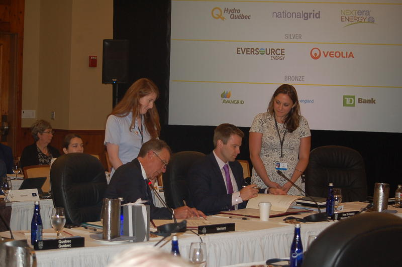 Vermont Gov. Phil Scott, left, and New Brunswick Premier Brian Gallant sign resolutions at Monday's annual conference of New England governors and eastern Canadian premiers. Gallant will host next year's meeting in St. John, New Brunswick.
