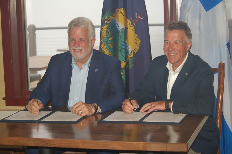 Quebec Premier Philippe Couillard, left, and Vermont Gov. Phil Scott sign a bilateral agreement Sunday in Stow