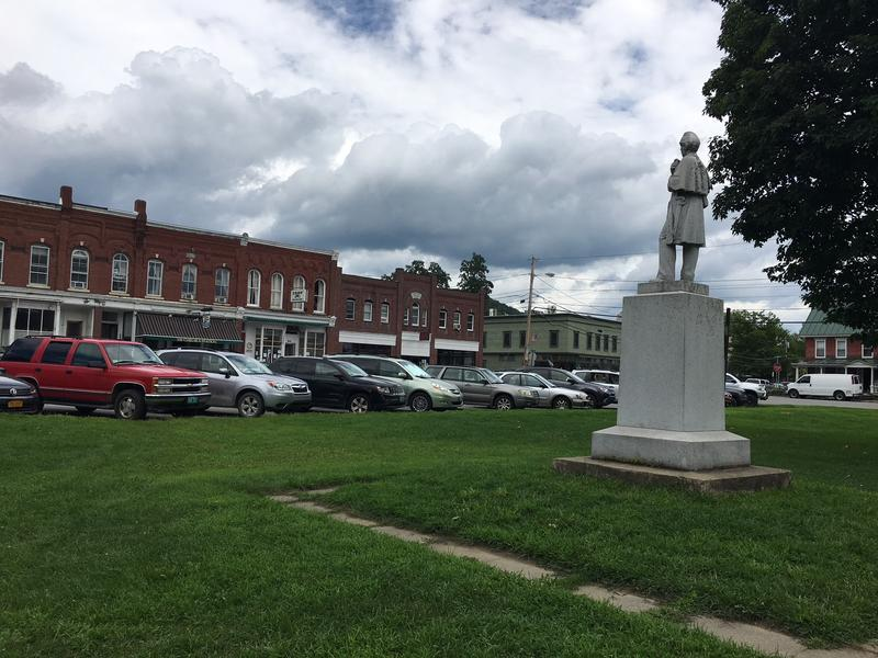 A scene of downtown South Royalton, Vt. With a statue, a line of parked cars and buildings in the background.