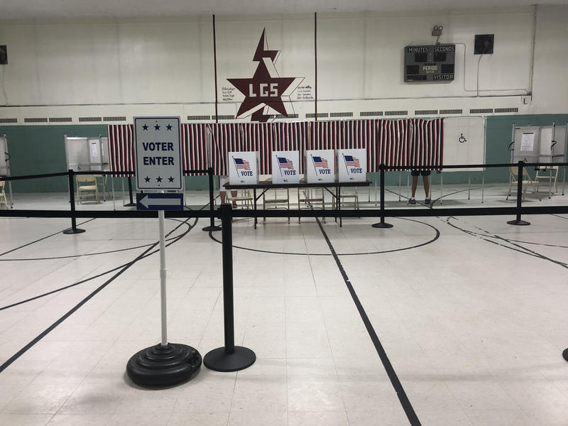 A polling place with a Vote Here sign and voting stations in a gymnasium-like room.