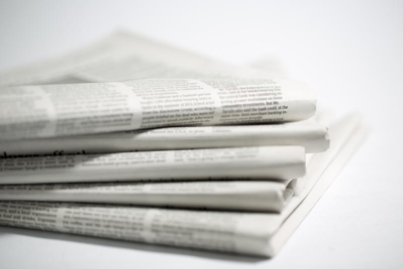 A stack of newspapers on a white background.