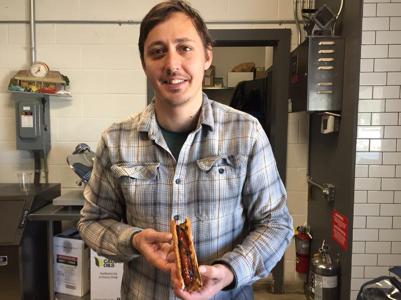 Wesley Genovart, co-owner of Honey Pie and SOLO Farm & Table restaurants holds a finished sausage.