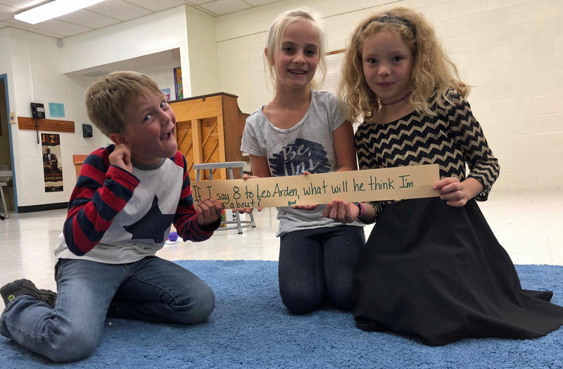 Third graders Max Becker, Anastasia Moshovetis and Eliza Frehsee, from left, hold up a question about Leo Arden, a character in one of Chris Harris' poems whose parents forgot to teach him the number eight.