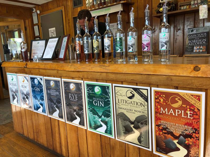 The bar at Smugglers' Notch Distillery with posters of products and bottles lining the counter.