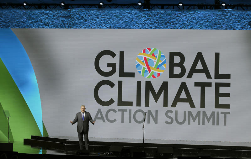 Al Gore stands on a stage with a sign that says Global Climate Action Summit in the background.