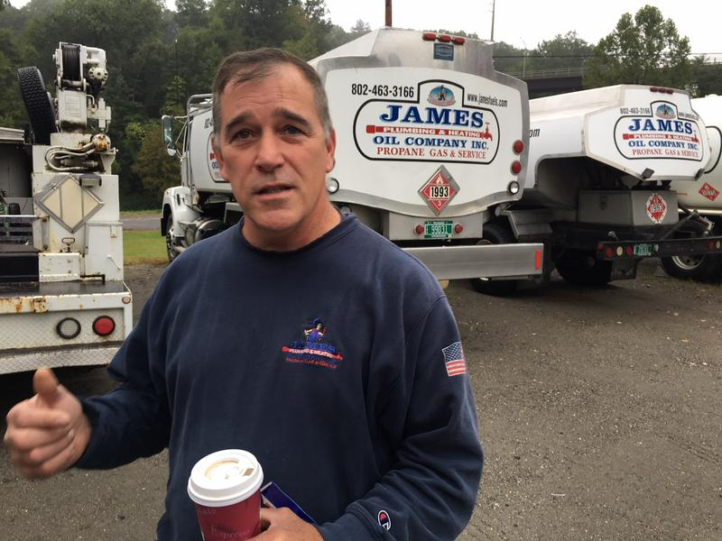 Tony James stands holding a drink cup in front of some James Oil Company trucks.