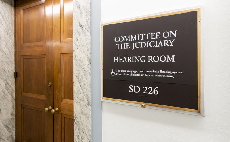 The sign outside a wood door that reads Committee on the Judiciary: This room is equipped with an assistive listening system. Please silence all electronic devices before entering. SD 226