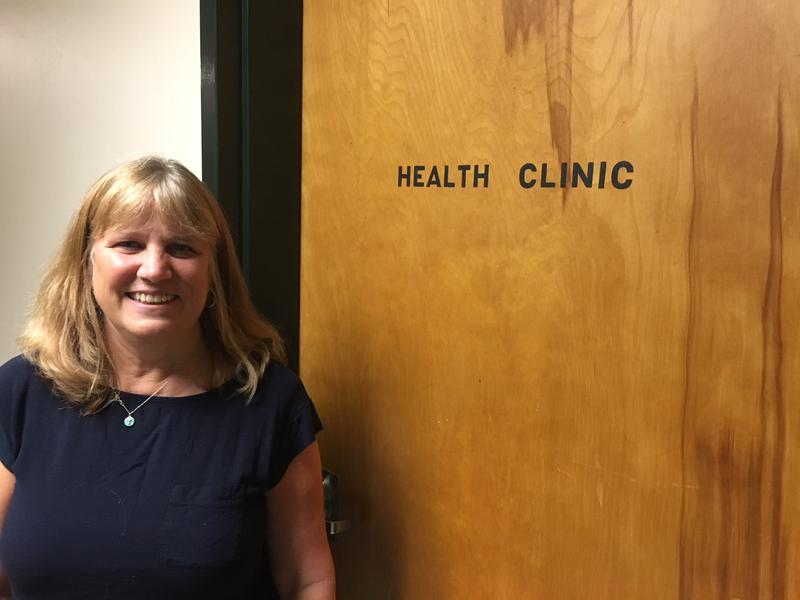 Springfield High School Nurse Jenny Anderson stands outside a shut wood door that says HEALTH CLINIC on it.