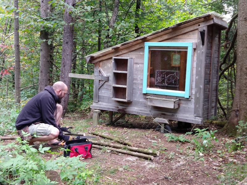 A man kneels on the ground outside of a tiny house in the woods of the Northeast Kingdom of Vermont.