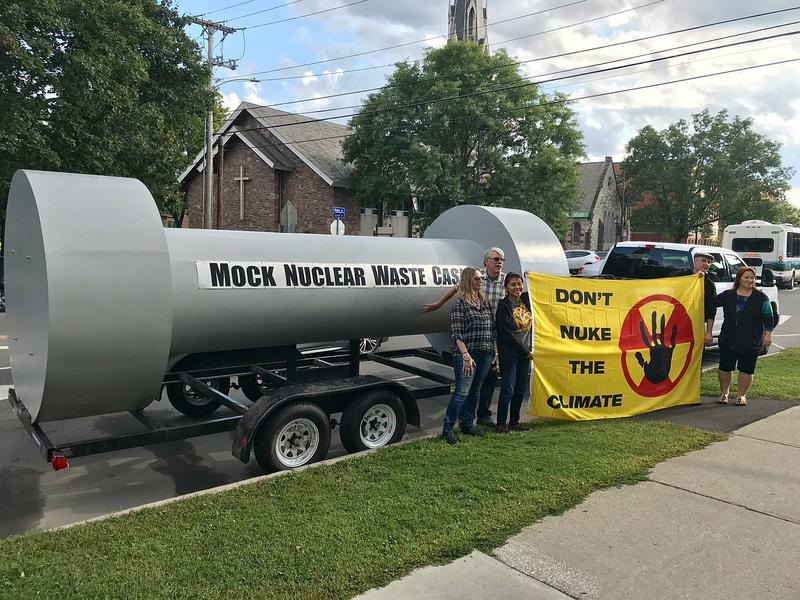"People stand in front of a ""mock nuclear waste cask"" and hold up a yellow sign that says Don't Nuke The Climate."