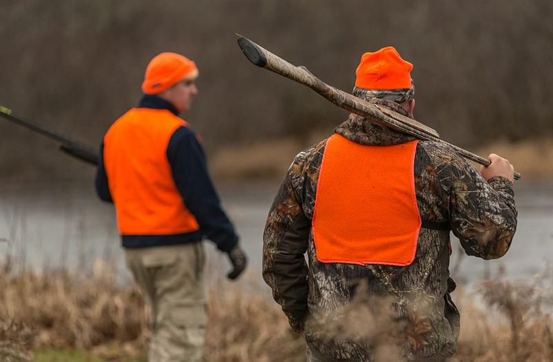 Two hunters depart from a hunting camp for an evening hunt wearing blaze orange, in line with advice from hunting safety experts.