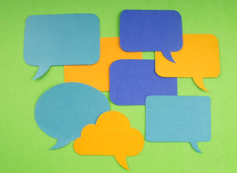 Teal, blue and orange speech, thought and chat bubble cut outs on a bright green background.