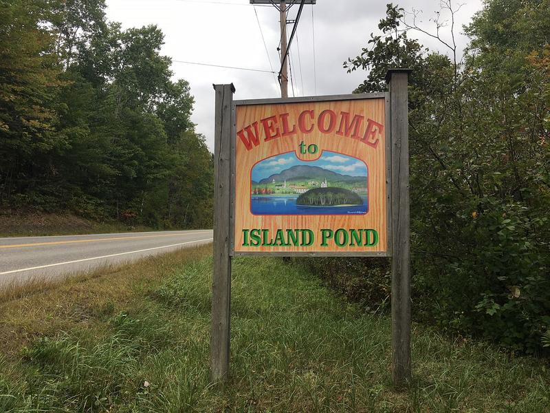 A welcome to Island Pond sign outside by a road.