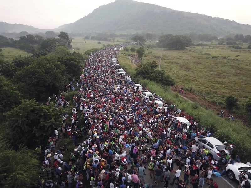 Members of a US-bound migrant caravan stand on a road after federal police briefly blocked their way outside the town of Arriaga, Saturday, Oct. 27, 2018.