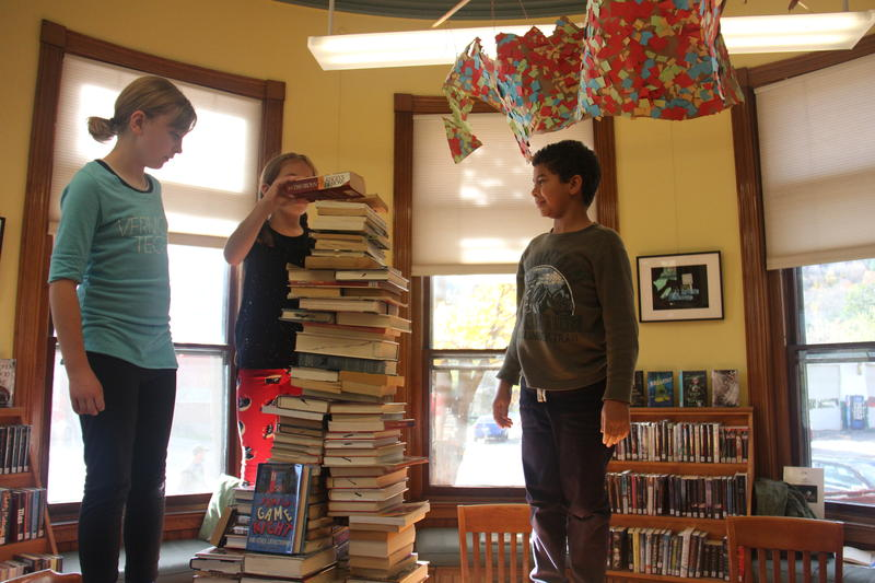 From left: Bailey Boardman, Cadyn Jarvis and Jonathan Cole  work on stacking library books.