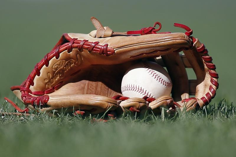 A baseball glove lies in the grass with a baseball in it.
