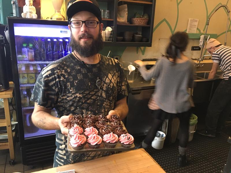 """Ben Keating, who works at Superfresh! Organic Cafe, offer gluten-free cupcakes to anyone who walks in with an """"I Voted"""" sticker."""