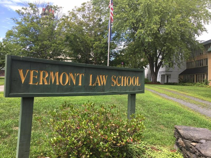 A Vermont Law School sign on campus with an American flag in the background.