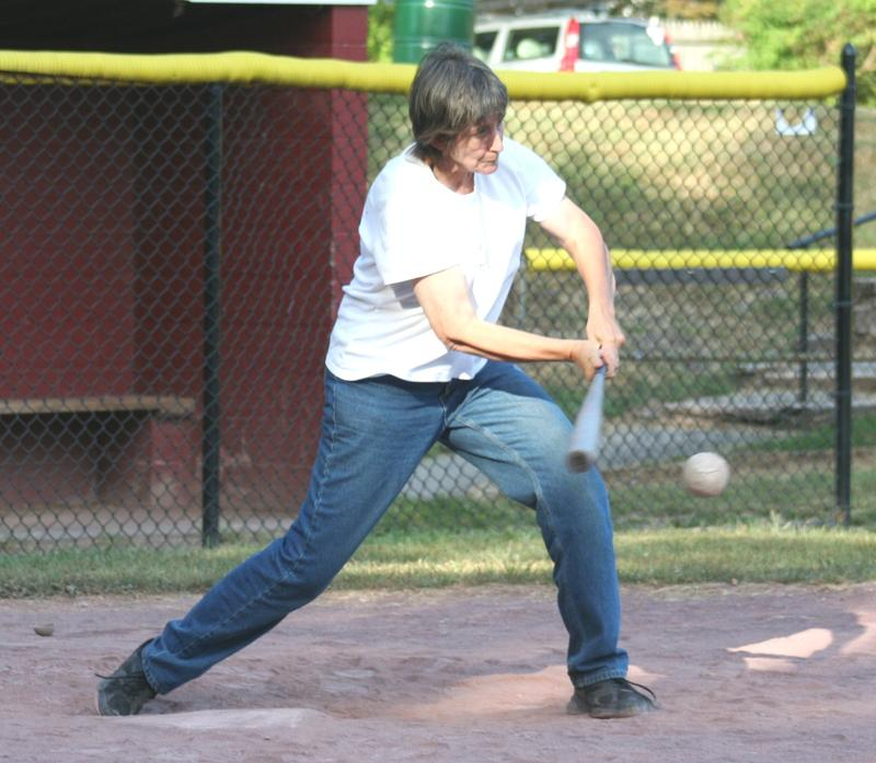 Anne Donahue mid-swing with a bat on a field